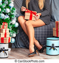 Woman with beautiful long tanned legs wearing grey sweater sitting in an armchair near by the christmas tree