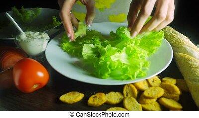 Woman with beautiful nail polish making Caesar chicken salad...