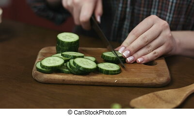 Woman with beautiful nails cutting cucumbers to prepare  a salad on a cutting board.