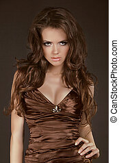 Woman with beauty long brown hair, model posing in elegant dress