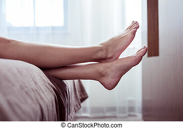 Woman with beige pedicure lying on nice big double bed in hotel room