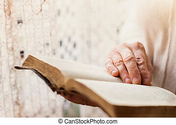 Woman with bible - Unrecognizable woman holding a bible in...