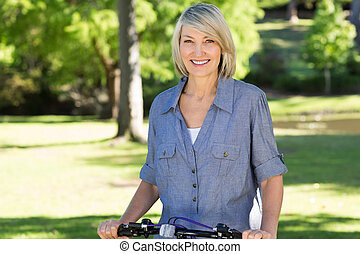 Woman with bicycle in park