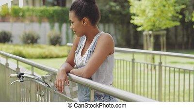 Woman with bicycle on bridge