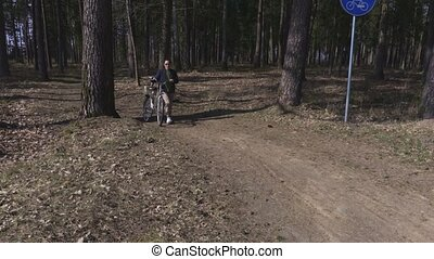 Woman with bicycle on path in park