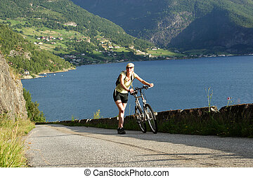 Woman with bicycle - Sporty woman walking with bike in thhe...