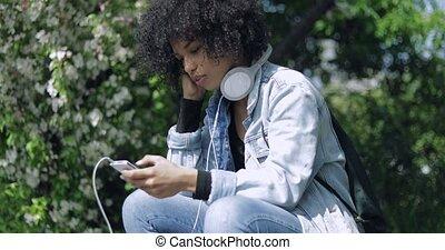 Woman with big headphones in park