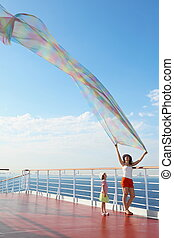 woman with big kerchief standing on deck of cruise ship. little girl looking at kerchief