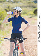 Woman with bike drinking water after biking in the...