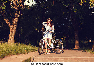 woman with bike outdoors.