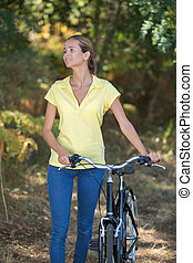woman with bike outdoors in the nature