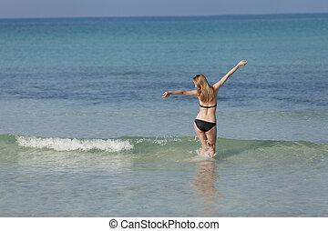 Woman with bikini in the sea jumping landscape