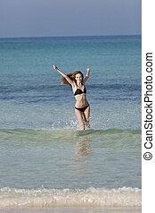 Woman with bikini in the sea jumping portrait