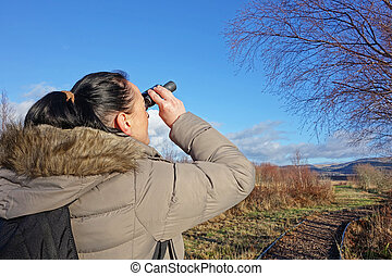 birdwatching - woman with binoculars birdwatching, looking...