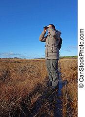 woman with binoculars birdwatching