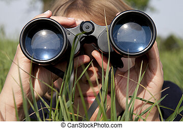 Woman with binoculars is discovering the surrouding -...