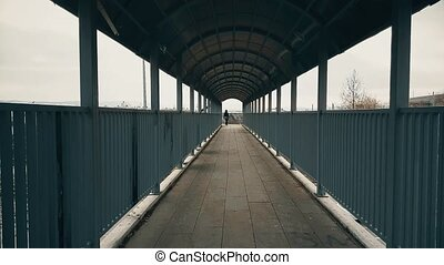 Woman with black coat walking across the footbridge over highway