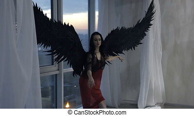 Woman with black wings poses against backdrop of large windows.