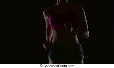 Woman with blond hair runs on a black screen. Silhouette. Slow motion. Close up