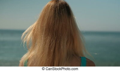 Woman with blond hair stands with her back against the shore.