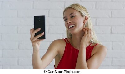 Woman with blond hair taking selfie - Beautiful young female...