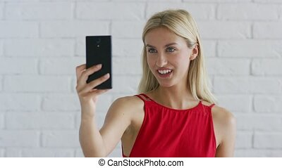 Beautiful young female with blond hair cheerfully smiling and touching neck while posing for selfie on background of white brick wall