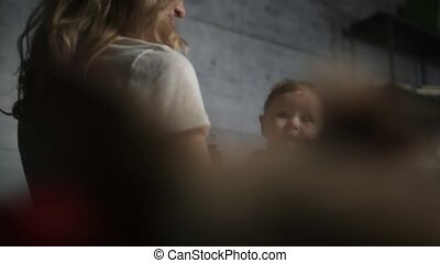 Woman with blonde curly hair kisses her little baby boy who sits on her laps and looking into camera