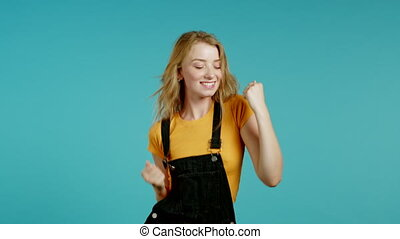 Woman with blonde hair very glad and happy, she shows yes gesture of victory, she achieved result, goals. Surprised excited happy lady on blue background.