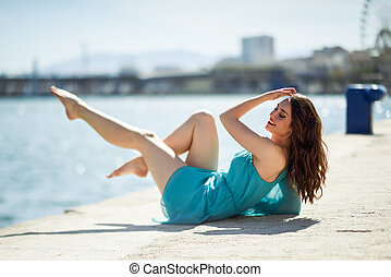 Woman with blue eyes wearing blue dress in the beach.