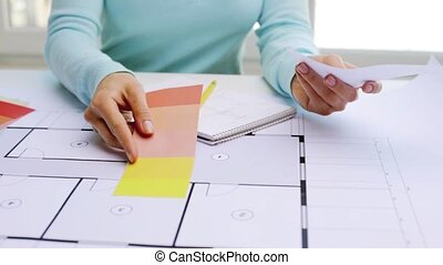 woman with blueprint and swatches choosing color - business,...