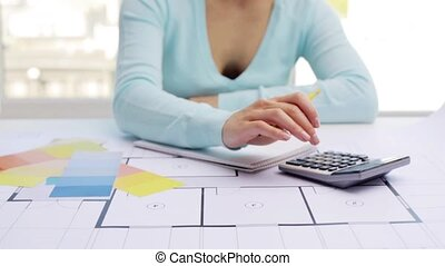 woman with blueprint counting on calculator