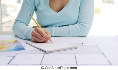 woman with blueprint drawing interior to notebook