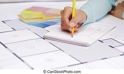 woman with blueprint drawing to notebook