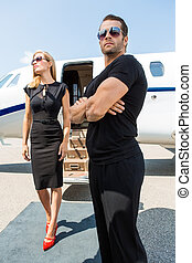 Woman With Bodyguard Against Private Jet