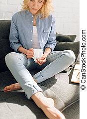 Woman with book drinks coffee on cozy black couch