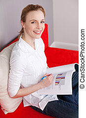 Woman With Book Sitting On Sofa