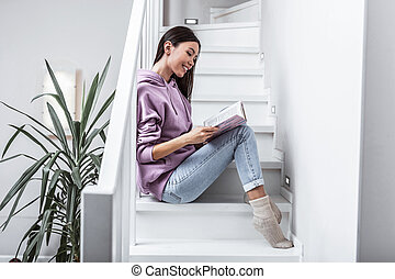 Woman wearing jeans and warm socks reading book sitting on stairs