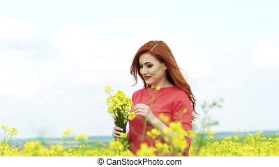 Woman with bouquet of rape blossom in the field, wind blowing. Slow motion
