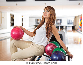 Woman With Bowling Ball Sitting On Rack