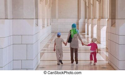 woman with boy and girl walks near building