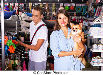 Woman with boy shopping dog accessories