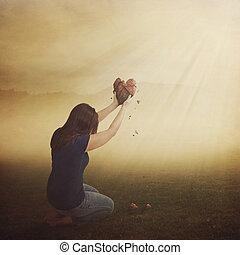 A woman with a broken heart in field.