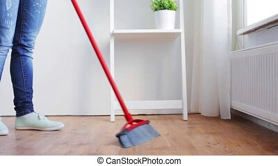 woman with broom cleaning floor at home - people, housework...