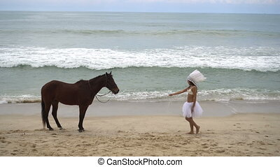 Woman with brown horse at the beach