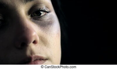 Sad woman crying in darkness after abuse