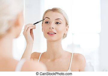 woman with brush doing eyebrow makeup at bathroom