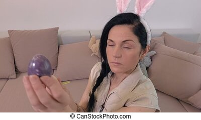 Woman with bunny ears keeping Easter egg and sitting on sofa