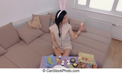 Woman with bunny ears preparing Easter eggs