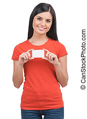 Woman with business card. Cheerful young woman holding business card and smiling while standing isolated on white