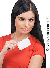 Woman with business card. Confident young woman holding business card while standing isolated on white